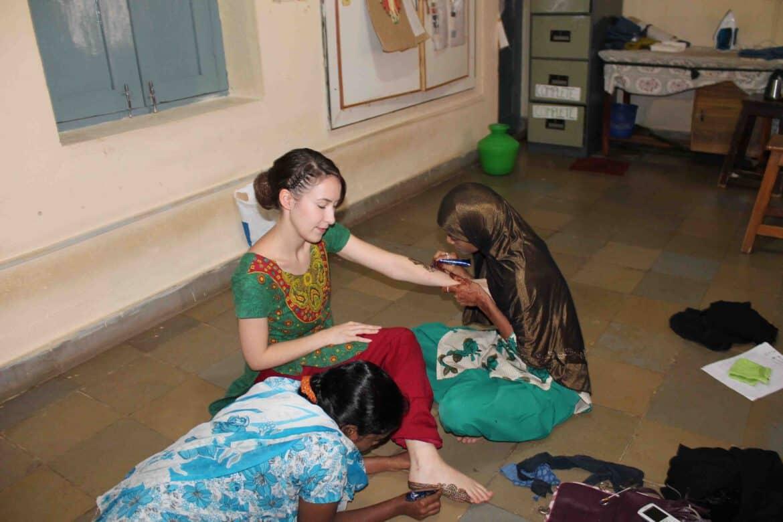 Unsere Praktikantin Eileen wird in der indischen Nähwerktstatt mit Henna bemalt.